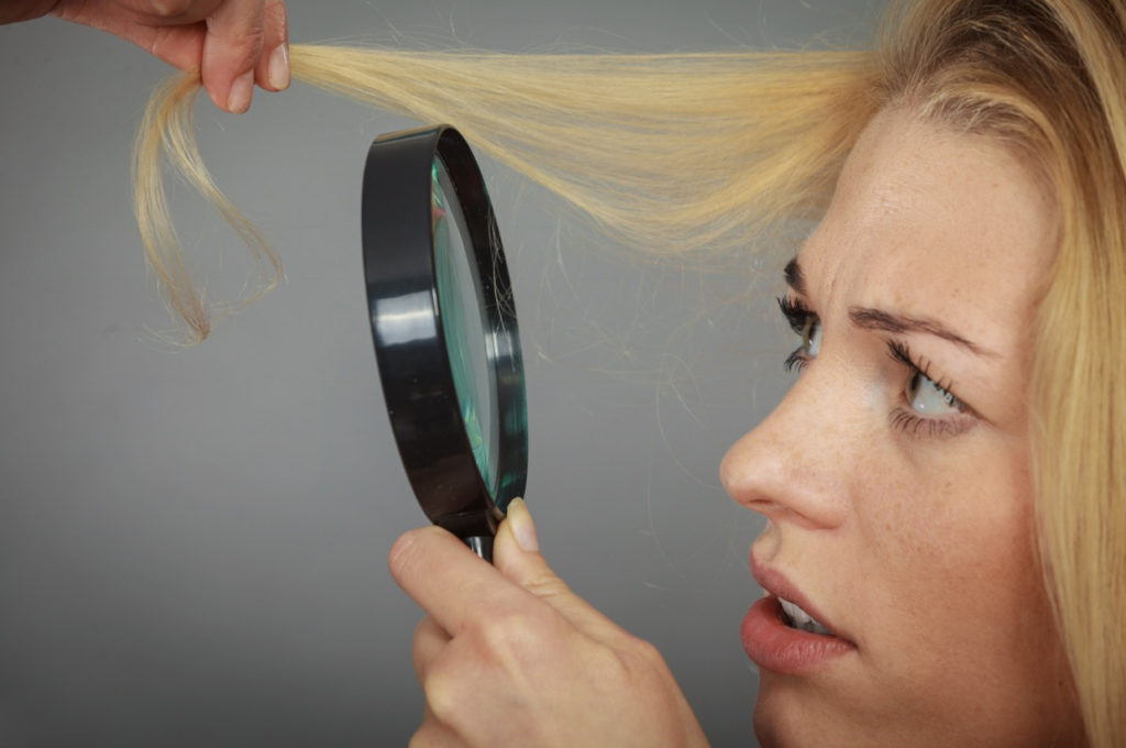 girl looking at hair through magnifying glass